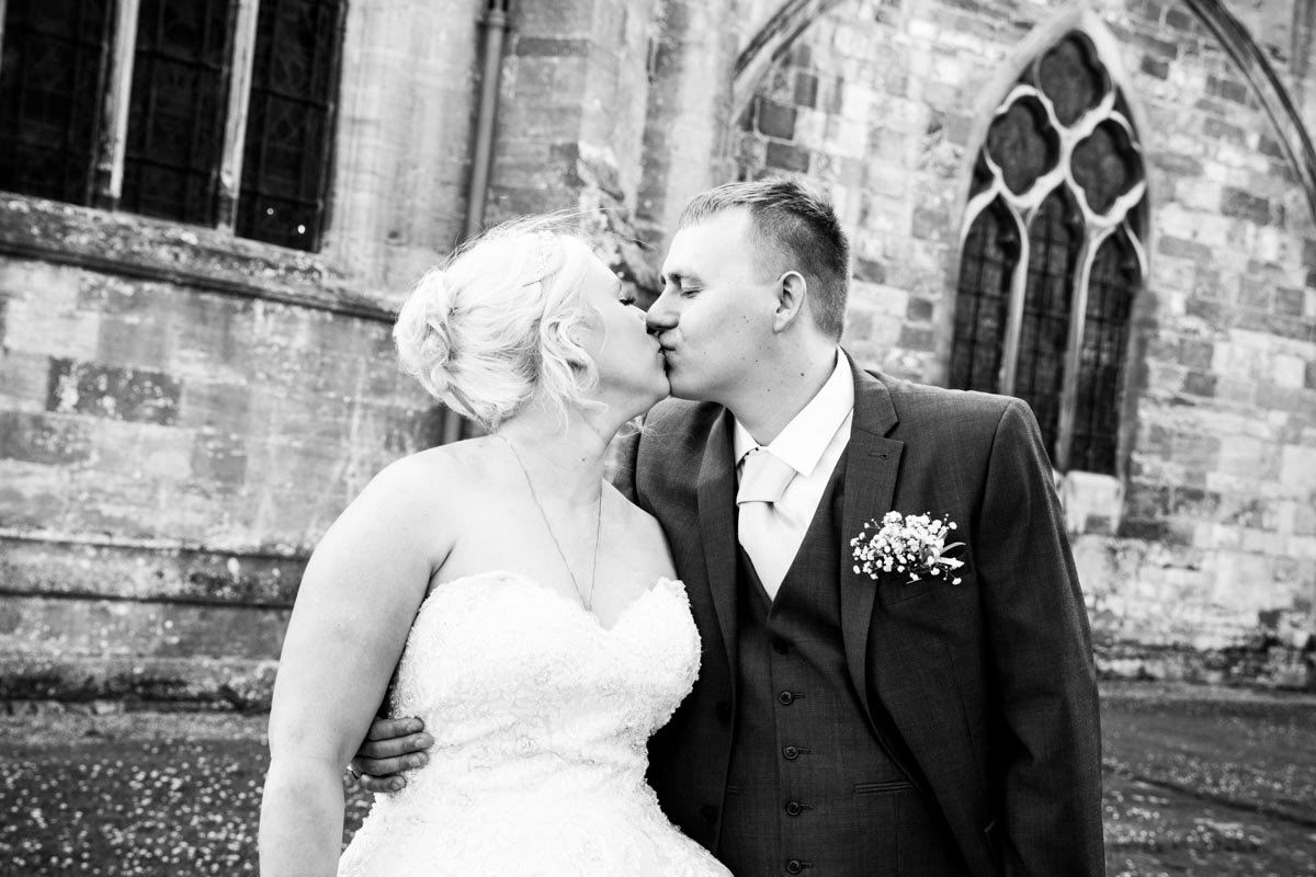 Bride and groom kissing outside the Tewkesbury Abbey.