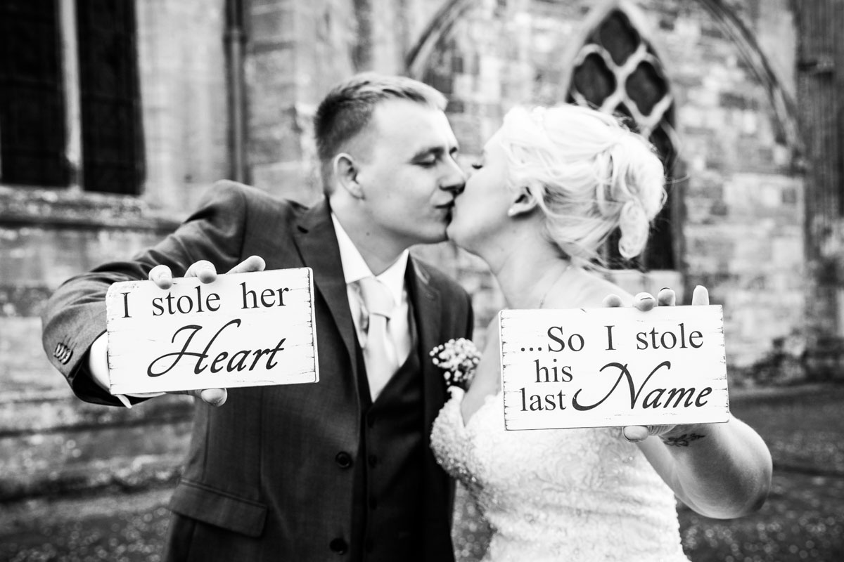 Newlyweds kissing outside Tewkesbury Abbey, holding signs. I stole her heart ..so I stole his last name.