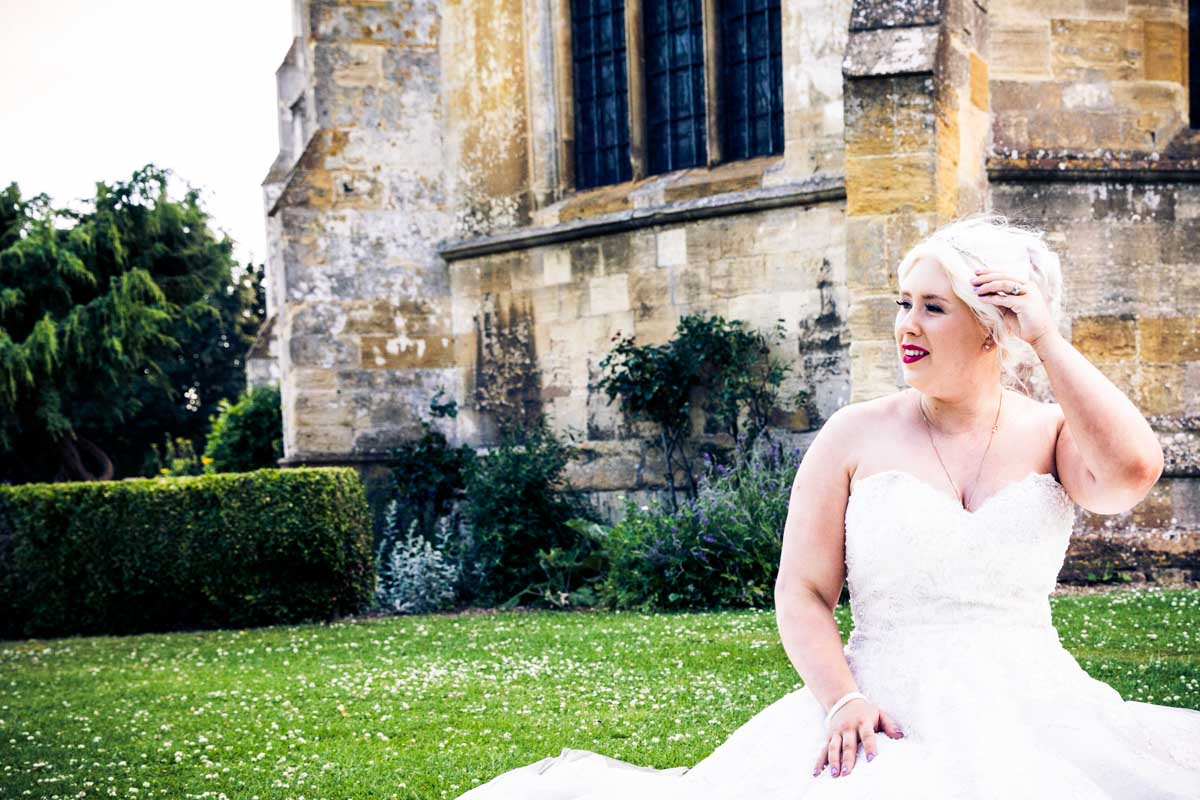 Bride sat on the grass outside the Tewkesbury Abbey.