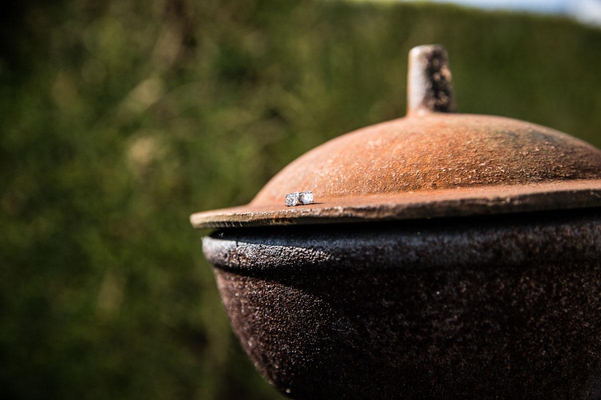 Diamante stud wedding earrings sat on a rusty garden pot.
