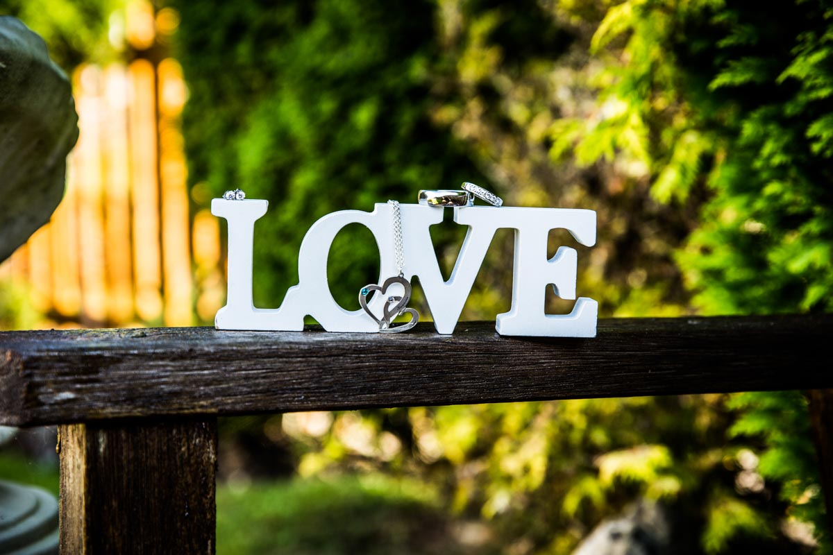 Love sign positioned on a bench, displaying the brides wedding jewellery.