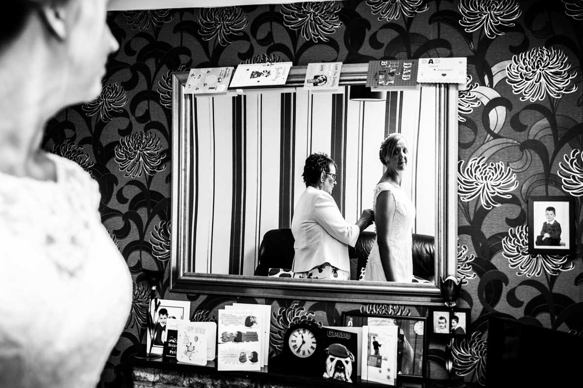 A mirror of the bride being put in her dress by her mother.