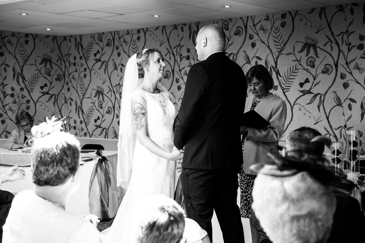 Bride and groom facing each other during wedding vows at the Cheltenham Regency Hotel.