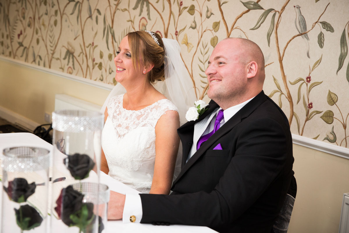 Bride and groom sat with the wedding register at the Cheltenham Regency Hotel.