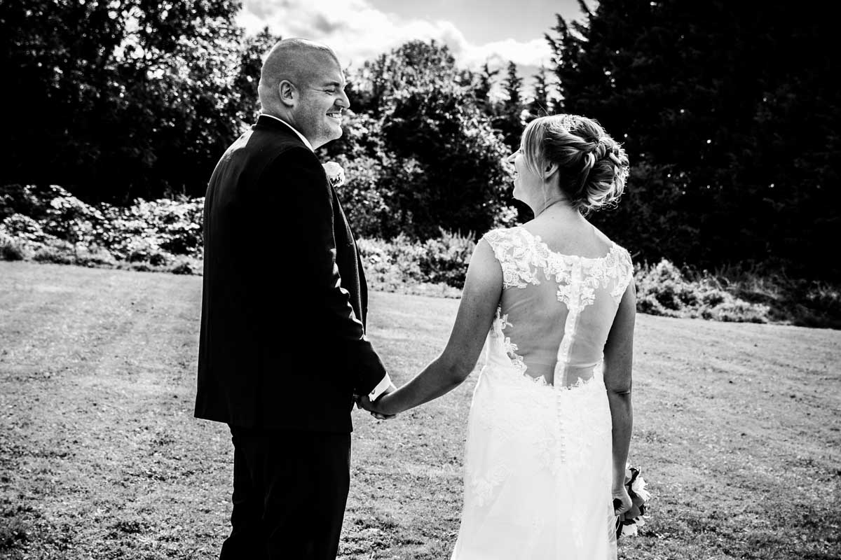 Bride and groom holding hands and looking at each other. Cheltenham Regency Hotel wedding.