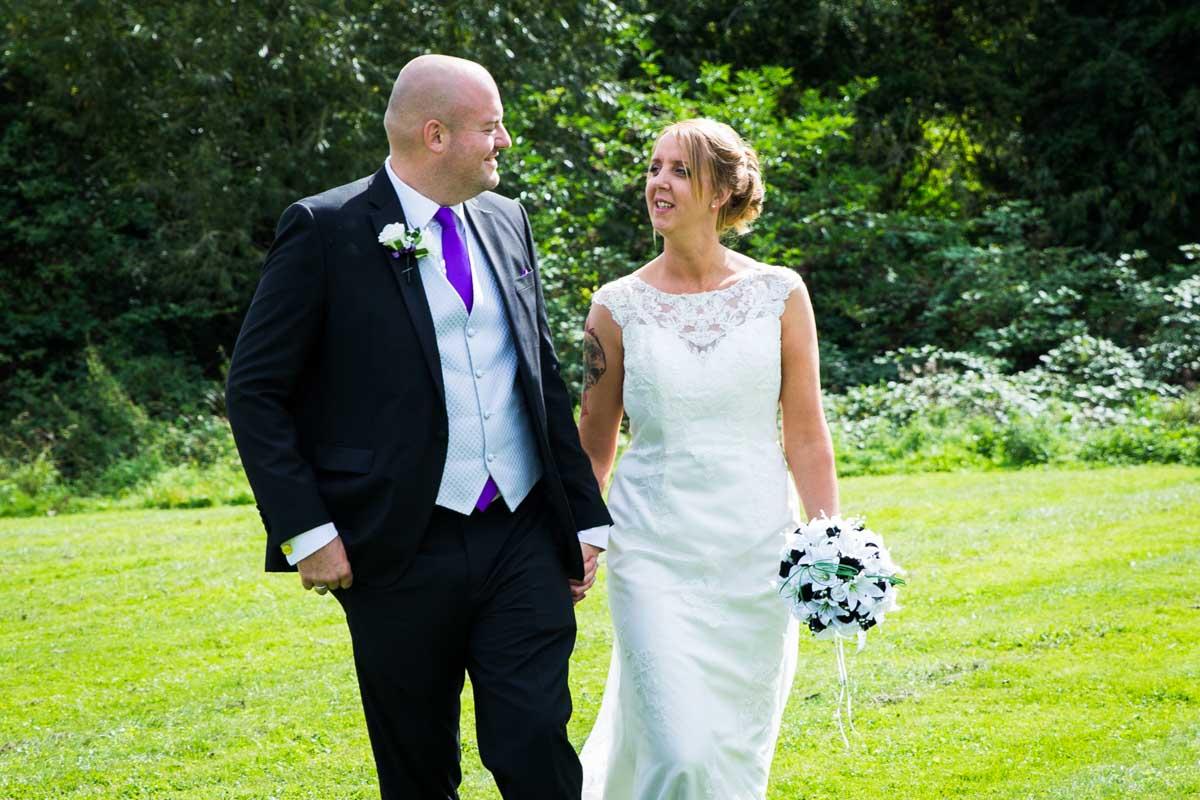 Cheltenham Regency Hotel wedding. Bride and groom walking in garden.
