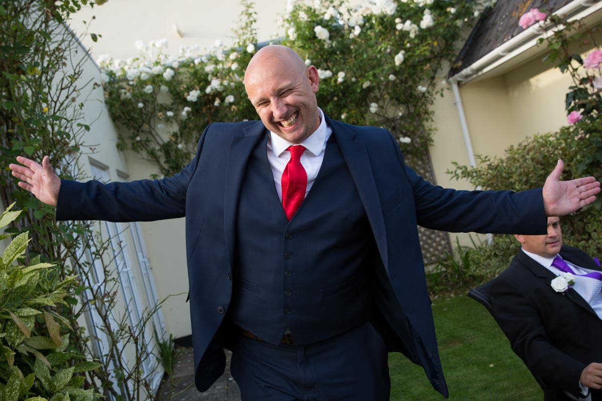Wedding guest with a blue suit and red tie at a Cheltenham wedding.