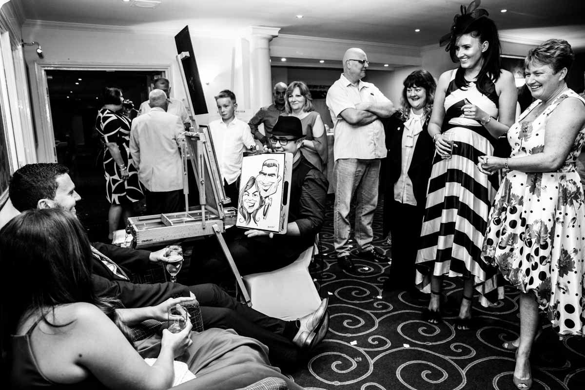 Wedding guests watching the caricaturist at a wedding.