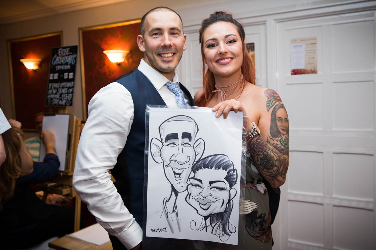 Two wedding guests holding up a caricature picture of themselves.