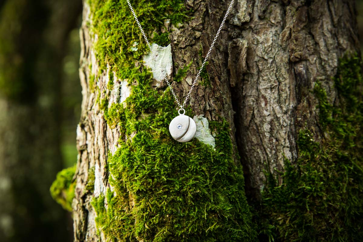 Wild by Descent moon necklace hanging in a tree. Jewellery commercial photography Glasgow