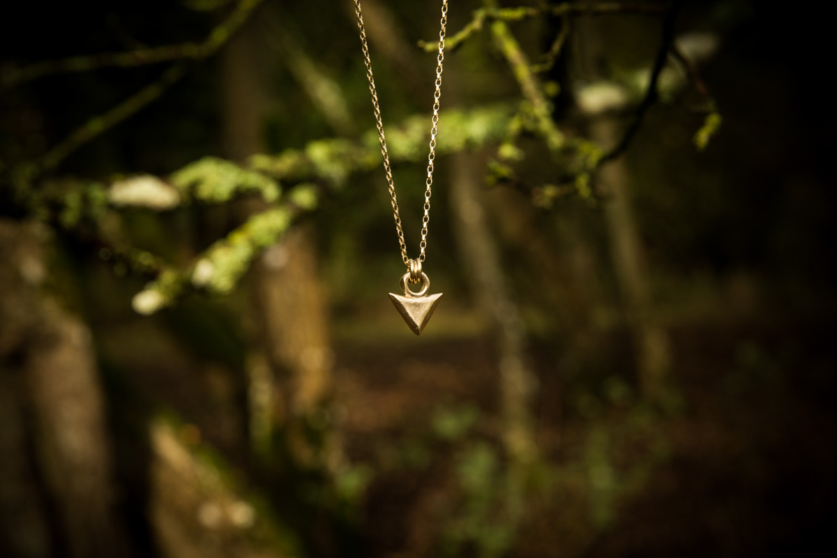 Handmade gold necklace hanging in a tree for jewellery commercial photography shoot. Glasgow photographer. Wild by Descent.