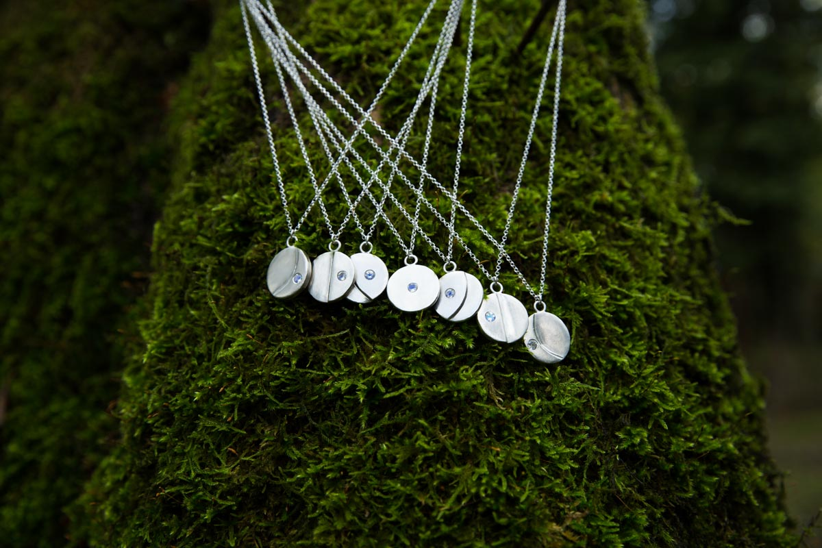 Handmade silver moon necklaces hanging in a tree. UK Commercial photographer.