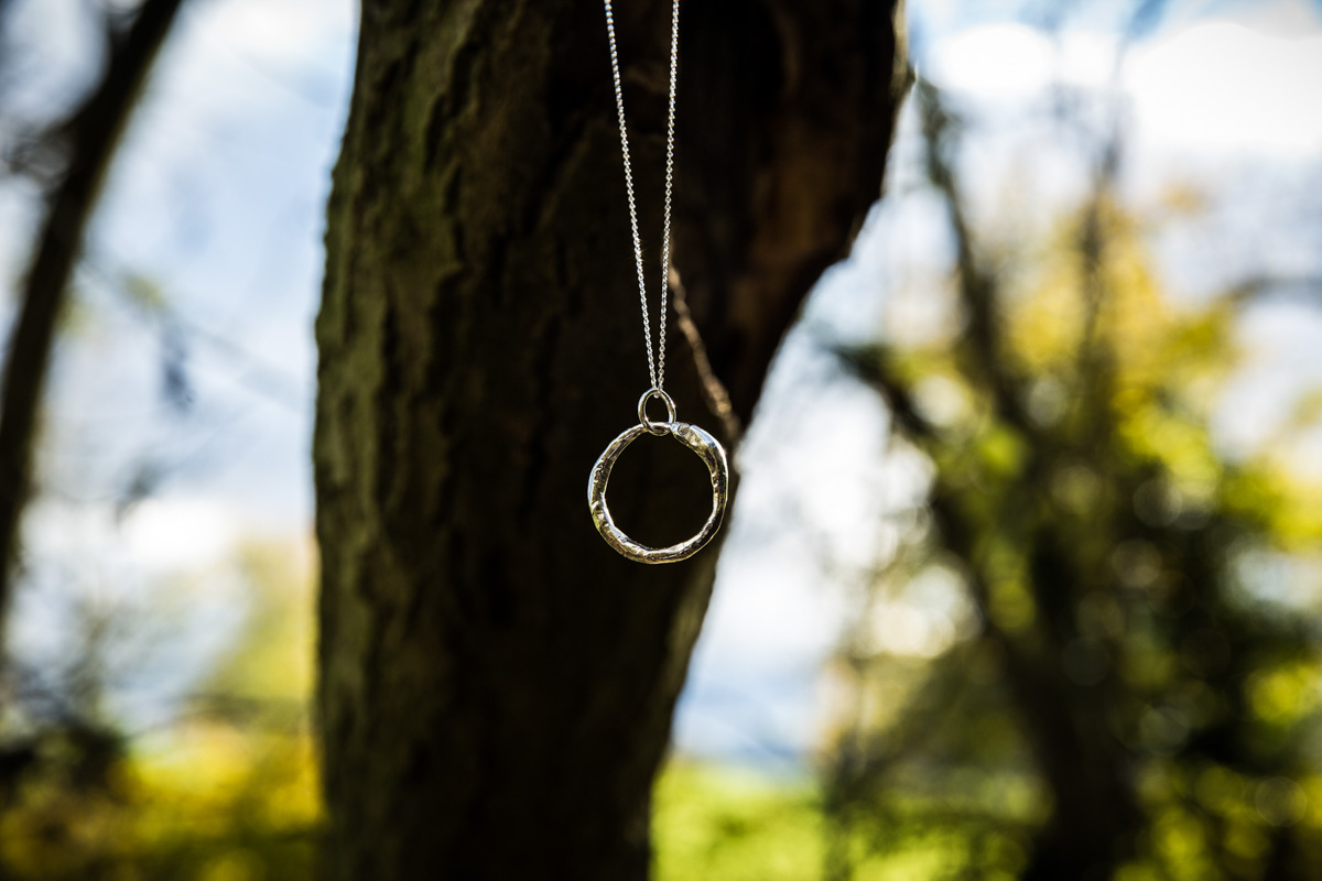 Handmade silver snake ring hanging in a tree during commercial photography shoot