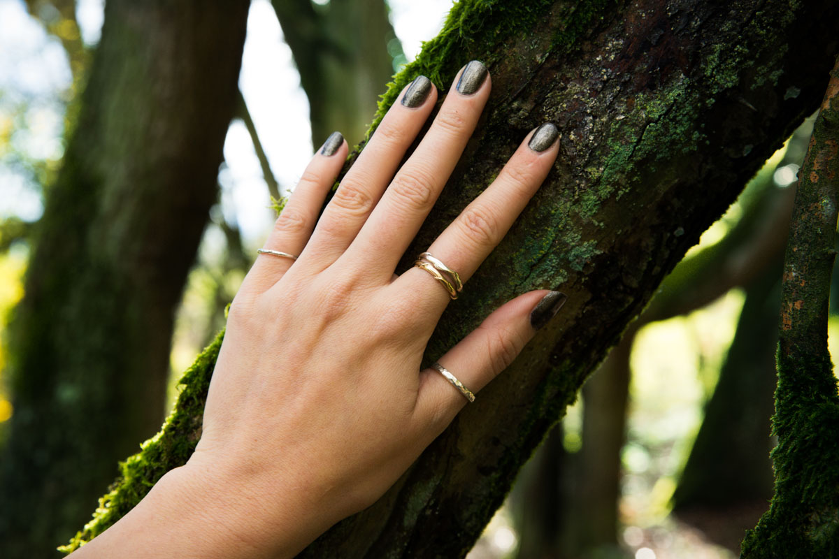 Hand modelling rings during a jewellery commercial photography shoot. Hand placed on a tree, wearing rings.