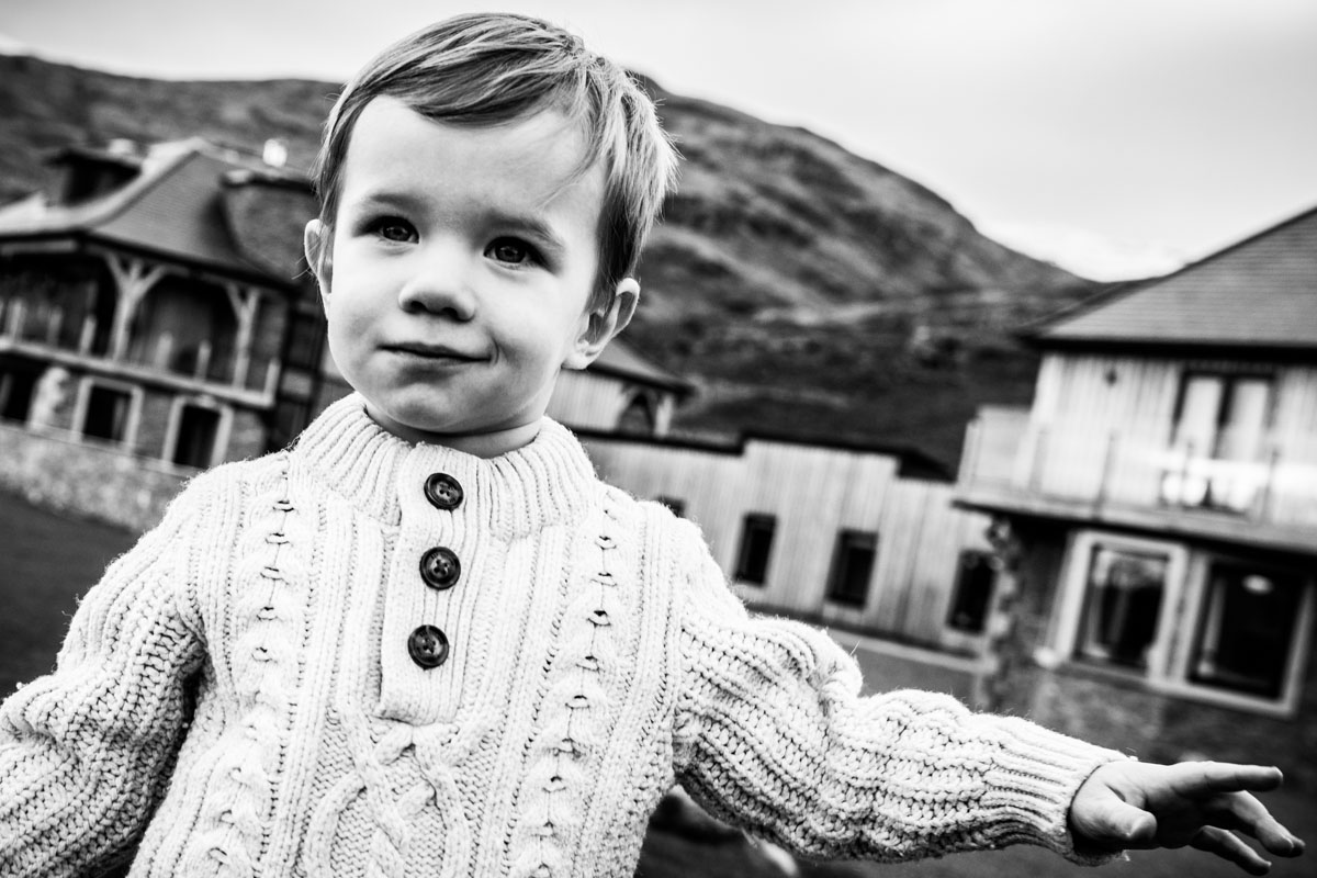Things to do in Lochgoilhead. A young boy smiling at the camera with the Carrick Castle Lodge in the background.