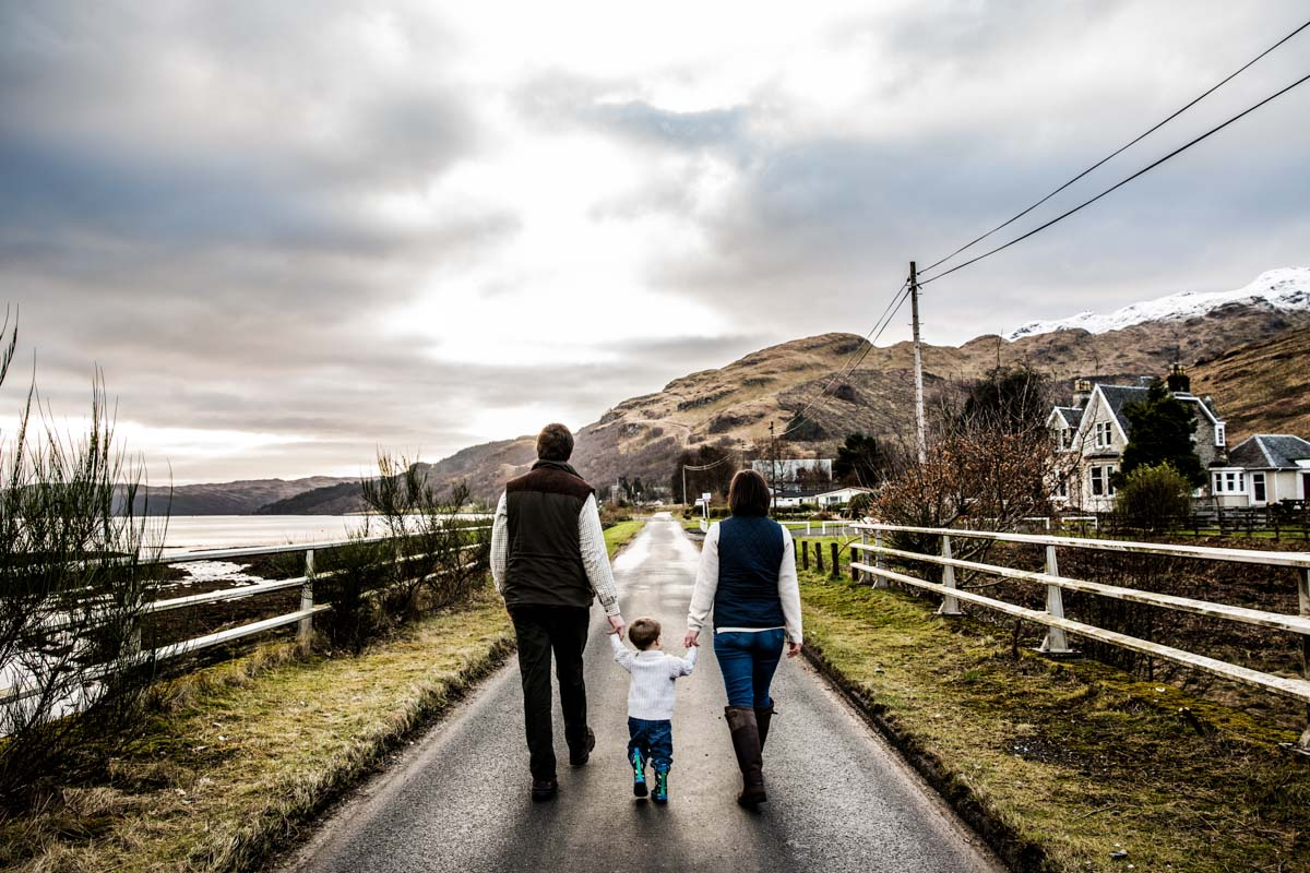 Argyll and Bute photographer. Family walking hand in hand away from camera, down a road during their Carrick Castle family shoot.