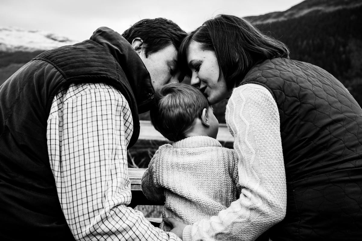 Lochgoilhead family photoshoot. A mum and dad kissing their son on the head during a Carrick Castle family photo shoot.