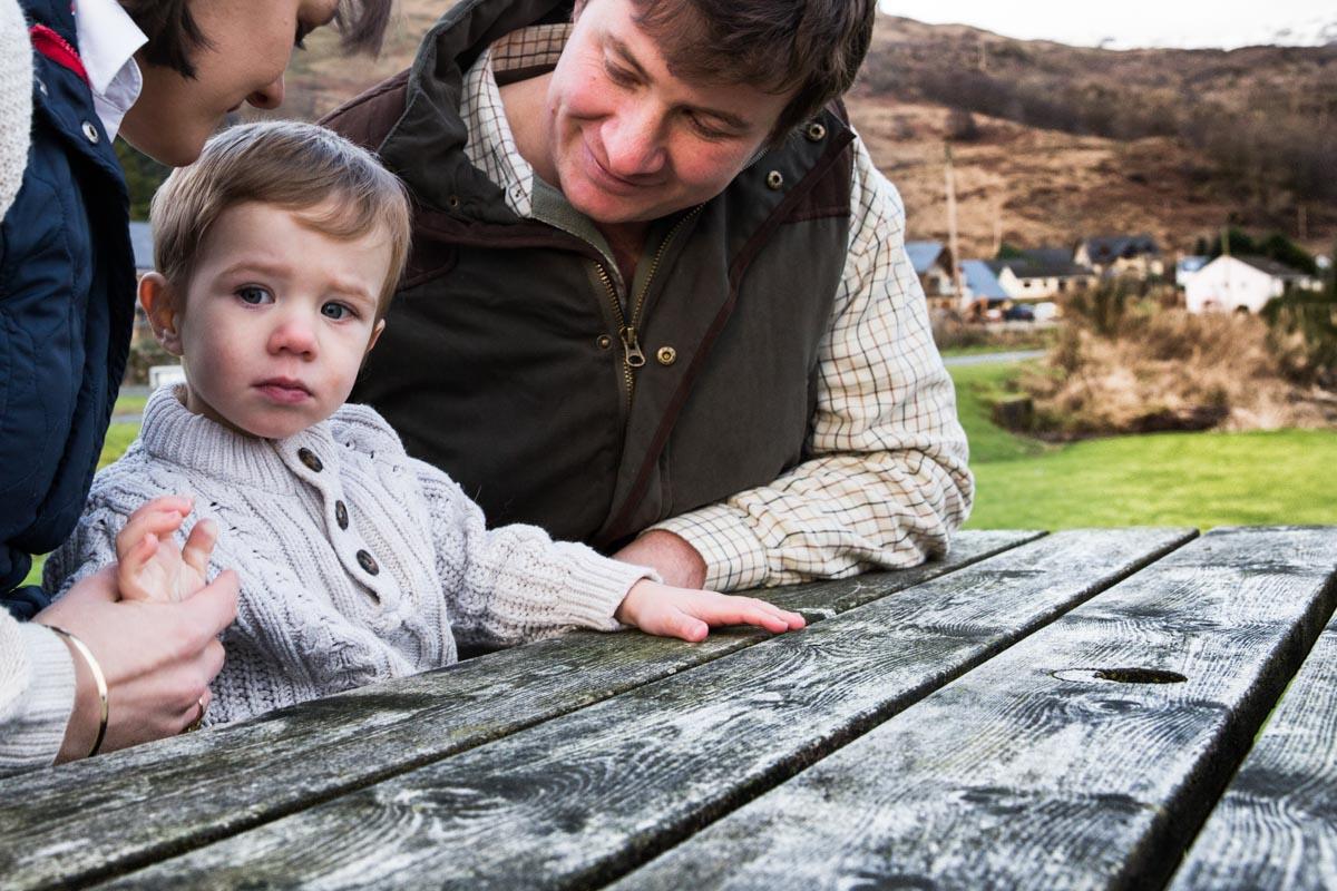 Lochgoilhead photographer. A little boy sat on an outdoor bench between his parents on the shores of Loch Goil.
