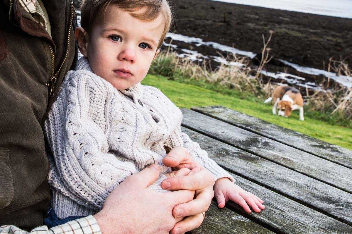 A little boy sat at a picnic bench during Loch Goil family photographs.