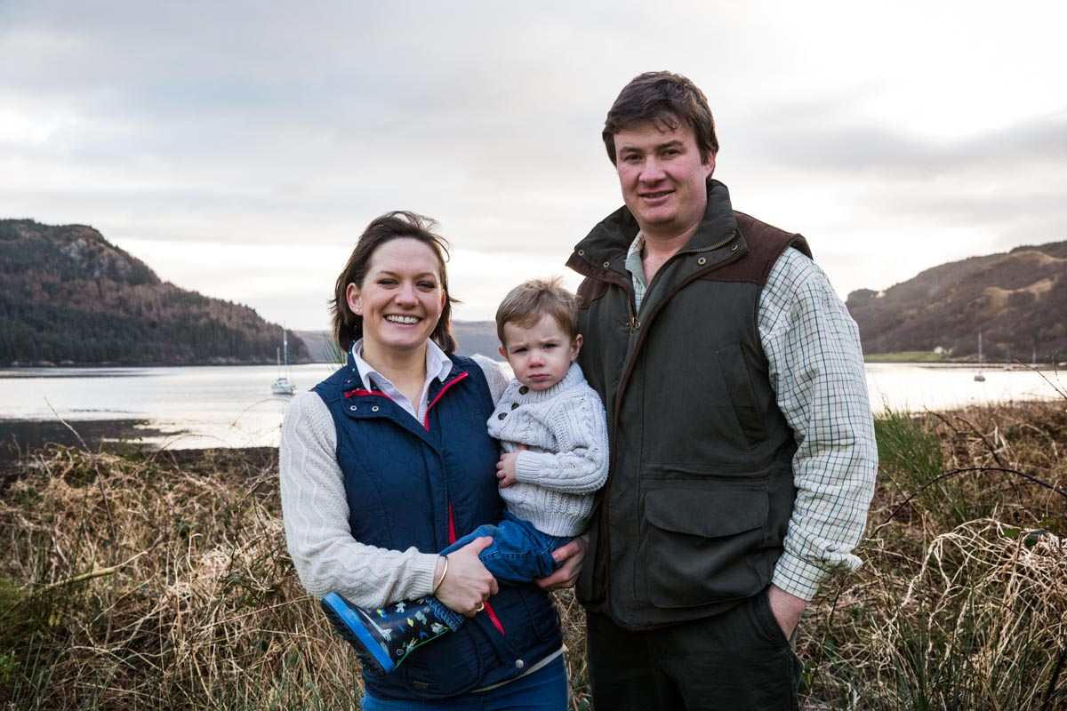 Parents stood holding their son by Loch Goil, during a family photo shoot.