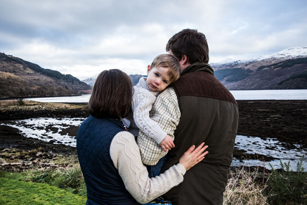 Parents cuddling their little boy and looking out over Loch Goil.