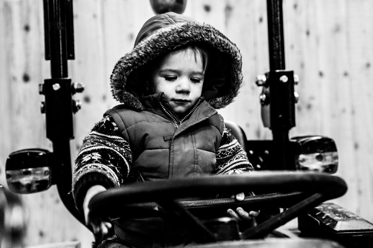 A little boy sat on a tractor in the Carrick Castle Estate barn.