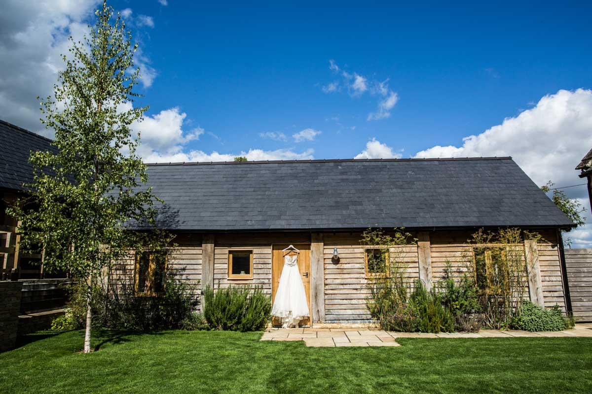 Upcote barn wedding dress hanging on the barn. Wedding photographer Cotswolds
