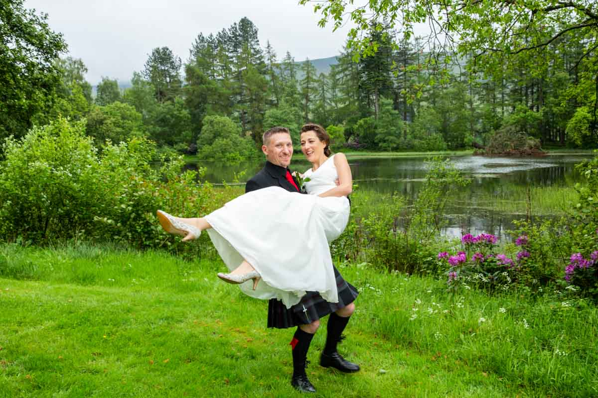 Bride and groom by Culcreuch Castle lake on their wedding day